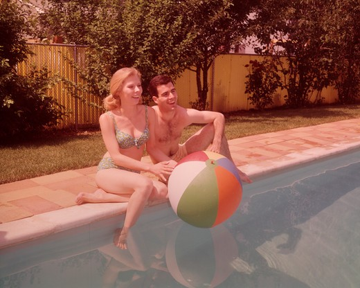 Stock Photo: 4186-2228 1960S Couple Sitting On Edge Of Swimming Pool