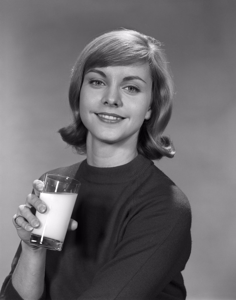 Stock Photo: 4186-2363 1960S Young Smiling Woman Holding A Glass Of Milk