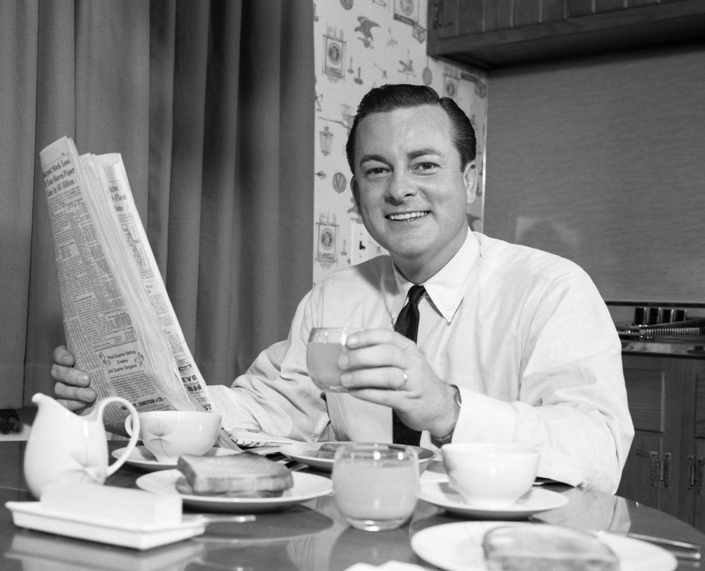 1960S Smiling Man Eating Breakfast Reading Newspaper  : Stock Photo