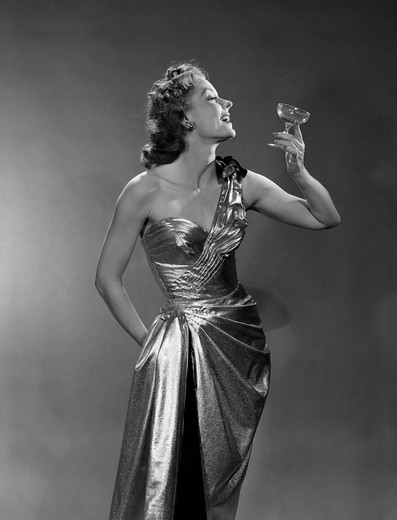 Stock Photo: 4186-2556 1950S Woman Wearing Metallic Evening Gown Holding Up Wine Glass Profile Indoor