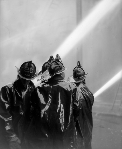 Stock Photo: 4186-2567 1920S Rear View Of Four Firemen In Black Slickers Squirting Two Hoses