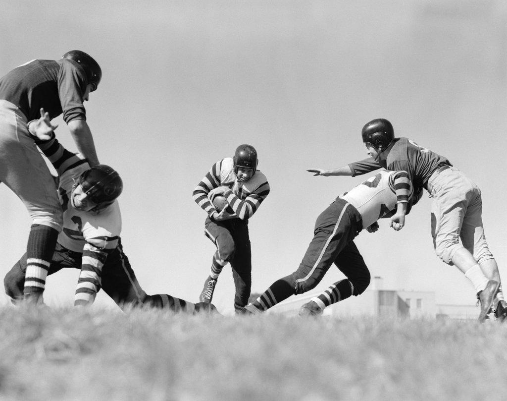 1940S Football Players Blocking Clearing Path For Player With Ball : Stock Photo