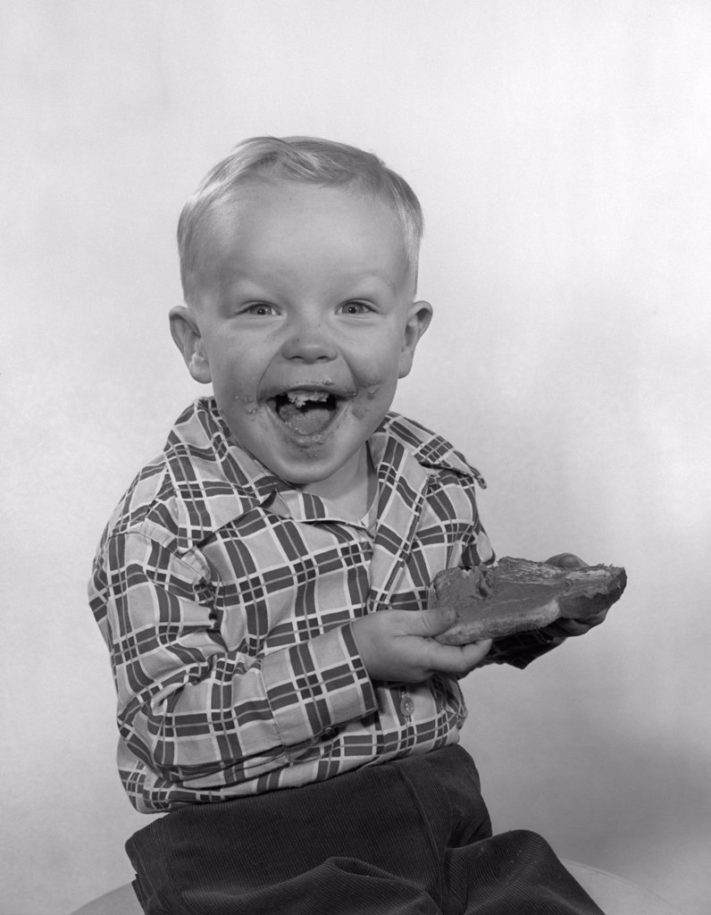 Stock Photo: 4186-2623 1950S Laughing Boy Wearing A Plaid Shirt With Jam On His Face And Mouth Holding A Slice Of Bread And Jam With Both Hands