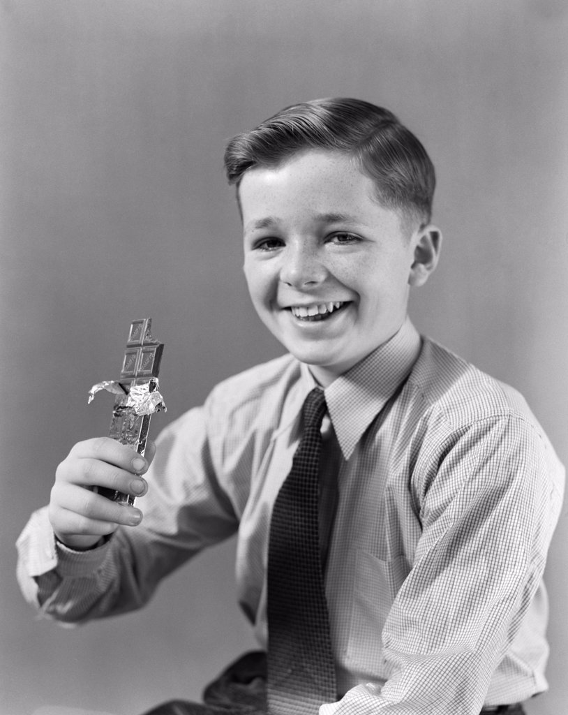 1940S Smiling Boy Holding Eating Candy Bar Chocolate Looking At Camera : Stock Photo