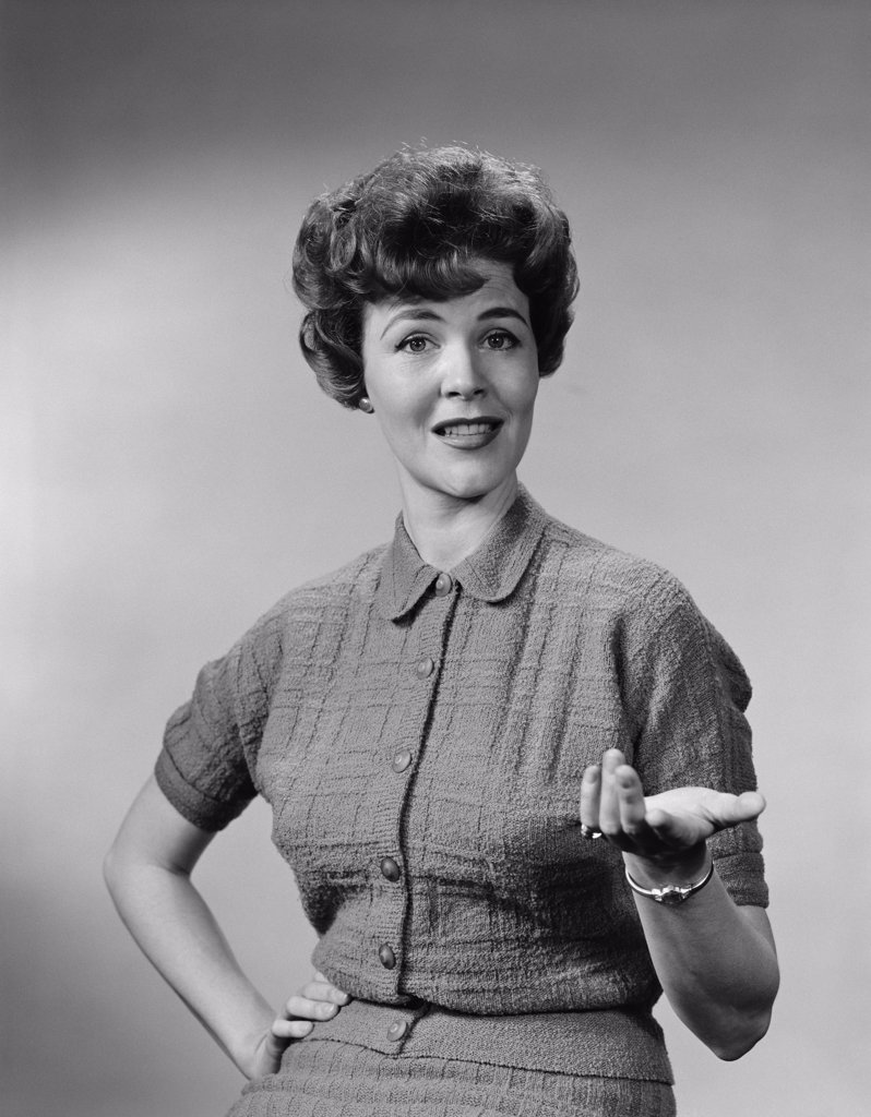 Stock Photo: 4186-2779 1950S Brunette Woman Knit Dress Offhand Gesture Serious Expression
