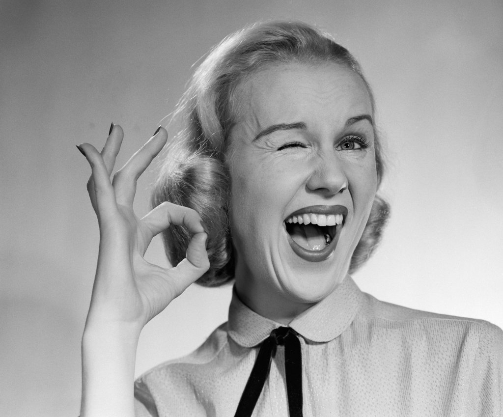 1950S Blond Woman Winking Eye And Making Ok Sign With Thumb And Finger : Stock Photo