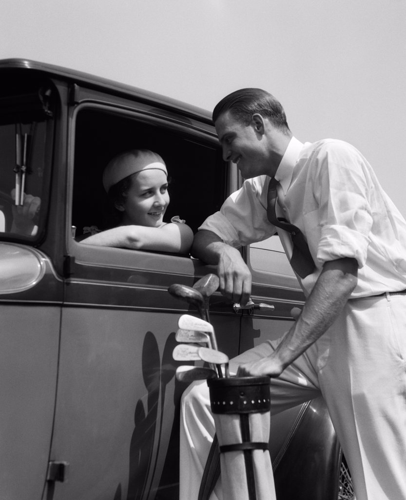 1930S Woman In Driver'S Seat Of Car Leaning Out Of Window Talking To Man Standing With Golf Bag : Stock Photo