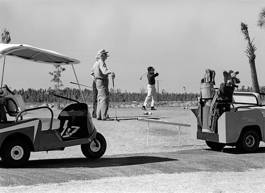 Stock Photo: 4186-2980 Three Men Playing Golf Teeing Off From Tee With Driver Near Golf Carts Outdoor 1960S