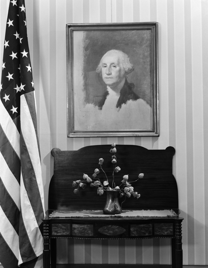 Stock Photo: 4186-3092 Framed Portrait George Washington Hanging Above Table With Flower Arrangement Next To American Flag