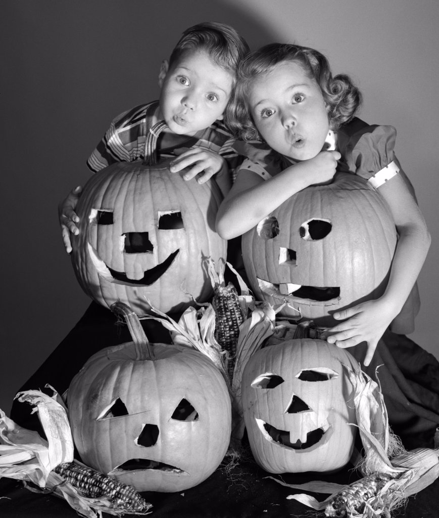 Stock Photo: 4186-3185 1950S Boy And Girl Standing Behind And Or Holding Four Jack-O-Lanterns With Indian Corn Making Spooky Faces