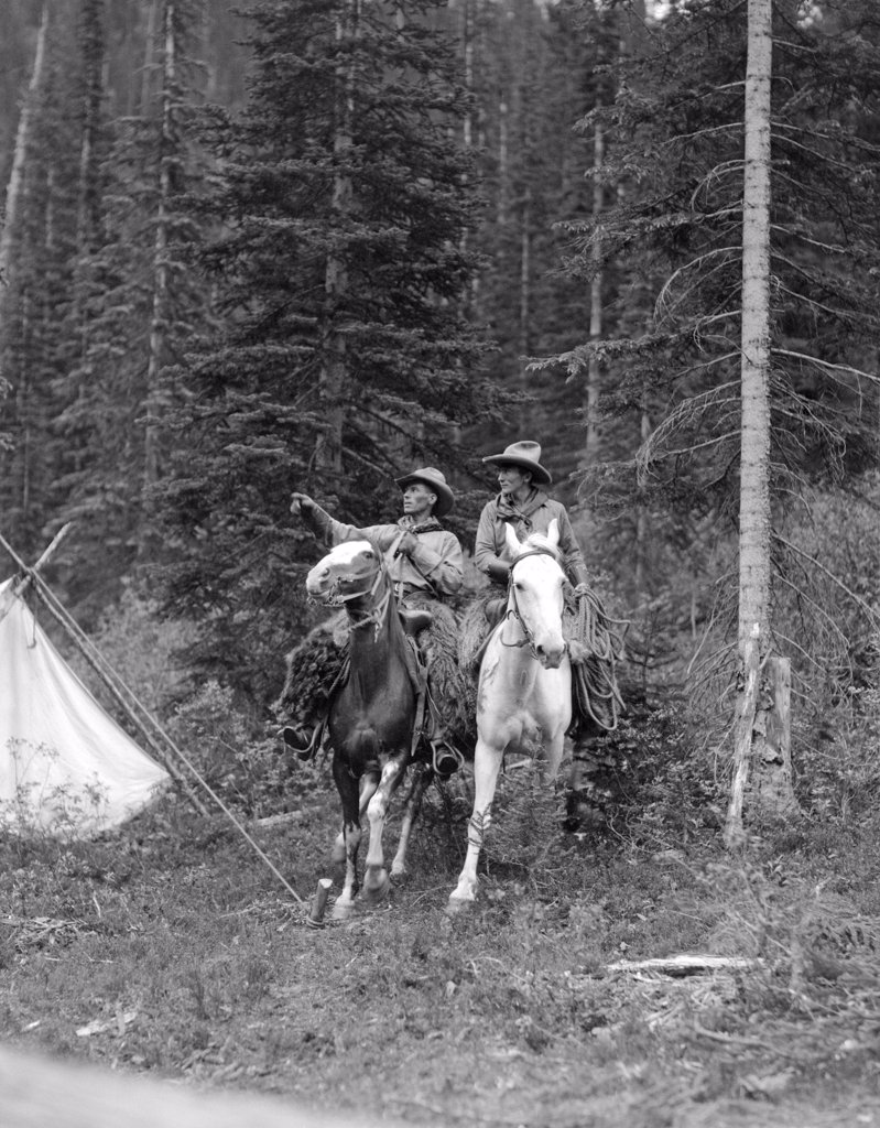 Stock Photo: 4186-3237 1920S Two Men Riding Horses Through Camp Grounds In Forest Cowboy Hat Tent Adventure Cowboys Both Are Wearing Angora Chaps