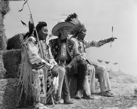 Stock Photo: 4186-3407 1940S Pair Of Indians In Full Costume Sitting On Bales Of Hay With Cowboy Between Them