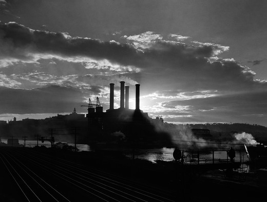 Stock Photo: 4186-3422 1930S Sunrise Sunset Behind Silhouette Of Industrial Power Plant With Smoke Stacks Near River And Railroad Tracks Outdoor