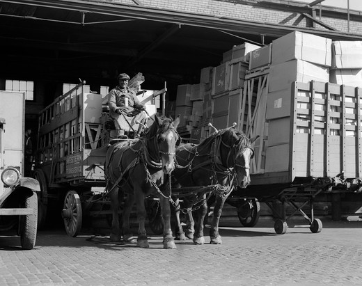 Stock Photo: 4186-3425 Turn Of The Century African American Man Pulling Wagon Drawn By Two Horses Out Of Truck Terminal