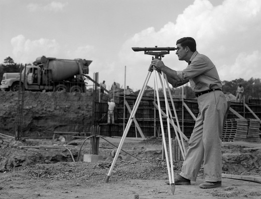 Stock Photo: 4186-3474 1960S Side View Of Worker Surveying Construction Site With Cement Mixer In Background