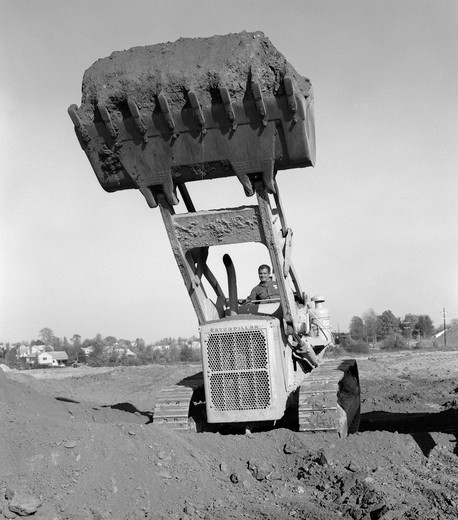Stock Photo: 4186-3485 1960S 1970S Man Operating Caterpillar Heavy Machinery Bull Dozer Lifting Shovel Full Of Dirt Soil Construction Site