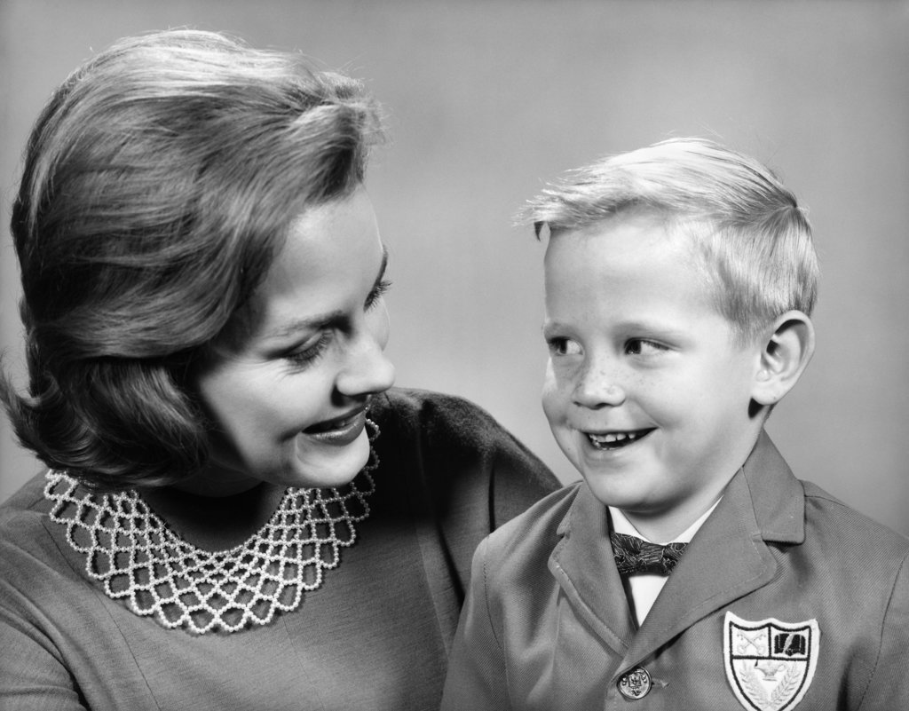 Stock Photo: 4186-3734 1960S Portrait Mother With Arm Around Son Dressed In School Uniform With Bow Tie & Emblem Crest On Jacket Mom Pearl Lace Collar