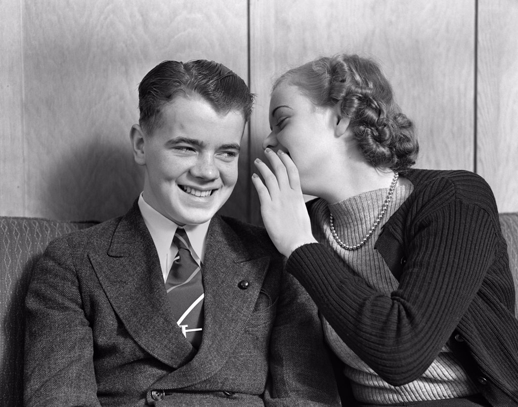 1930S 1940S Young Teenage Couple Sitting On Couch Girl Whispering Secret Into Smiling Boy'S Ear : Stock Photo