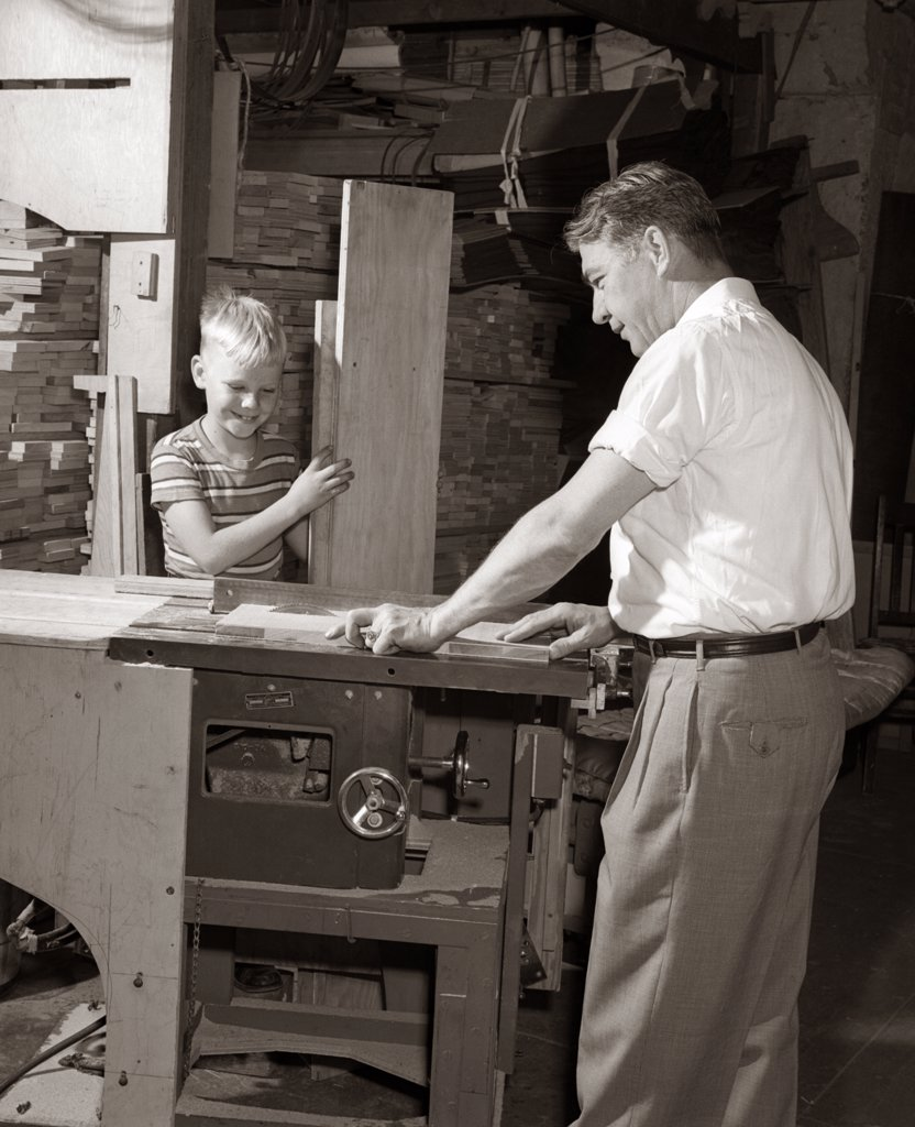 Stock Photo: 4186-3965 1930S 1940S 1950S Man Father Cutting Wood Board On Table Saw Teaching Boy Son Carpentry