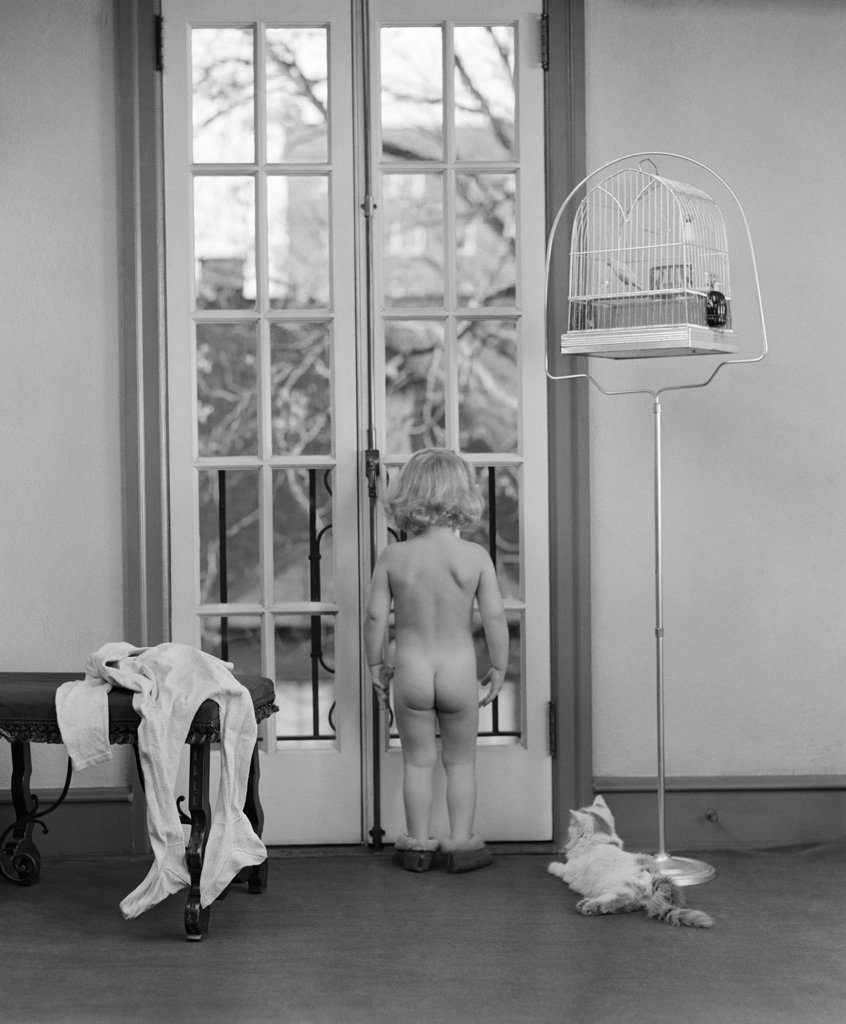 Stock Photo: 4186-3970 1950S Young Girl Nude Back To Camera Facing Out Window Clothes Beside Her Cat And Bird In Birdcage Next To Her