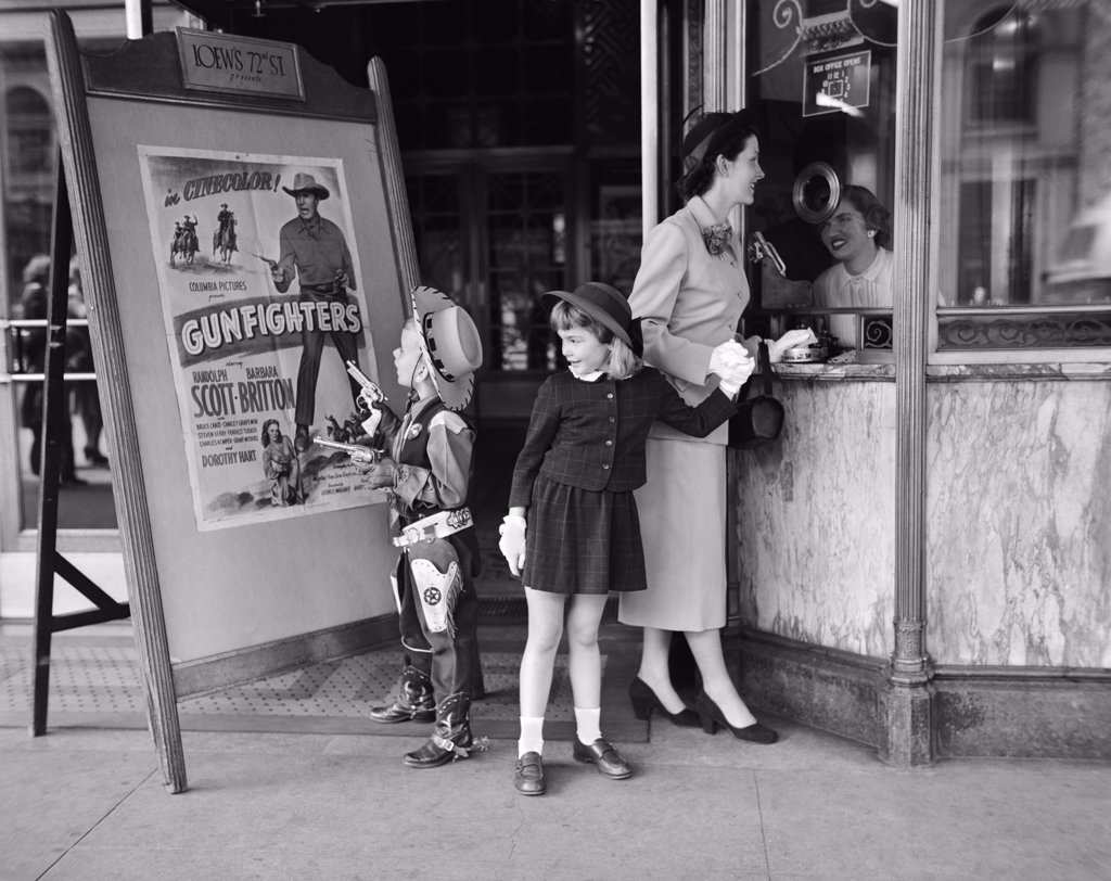 Stock Photo: 4186-4067 1950S Mother 2 Children Buying Tickets To Movie Matinee Boy Wearing Cowboy Costume