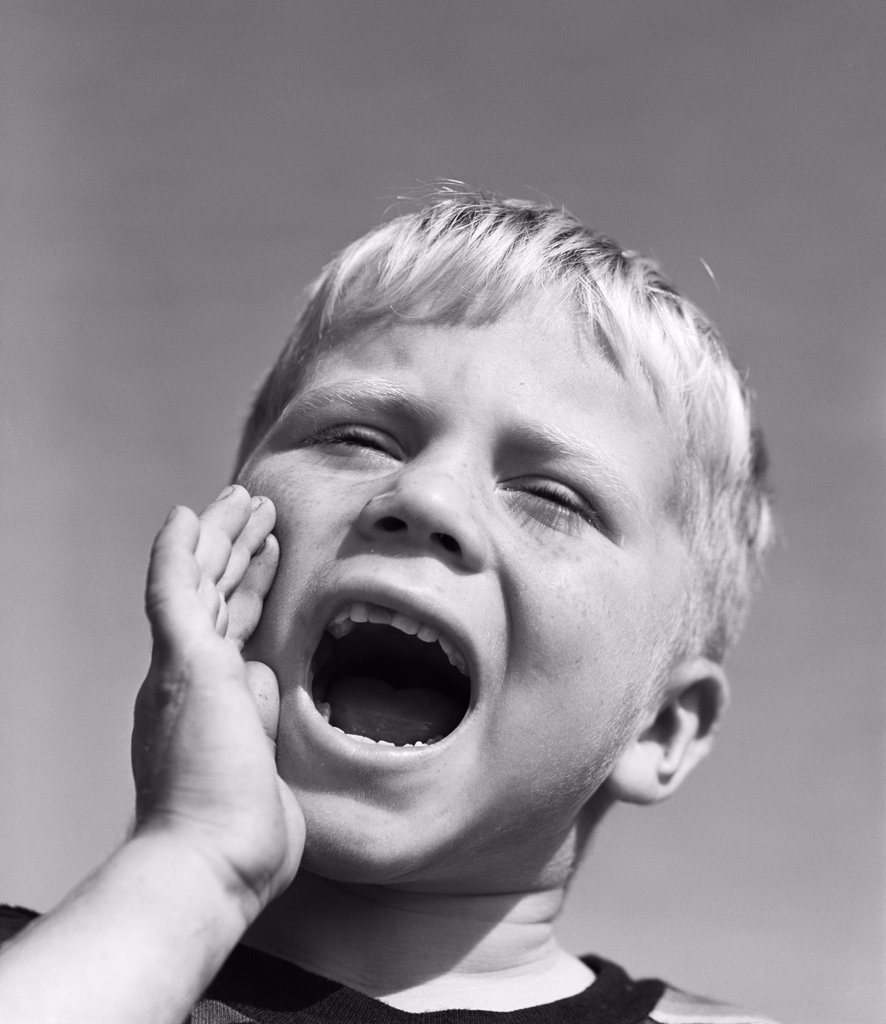 1950S Blond Boy With Eyes Closed And Hand Cupping A Wide Open Mouth Shouting : Stock Photo