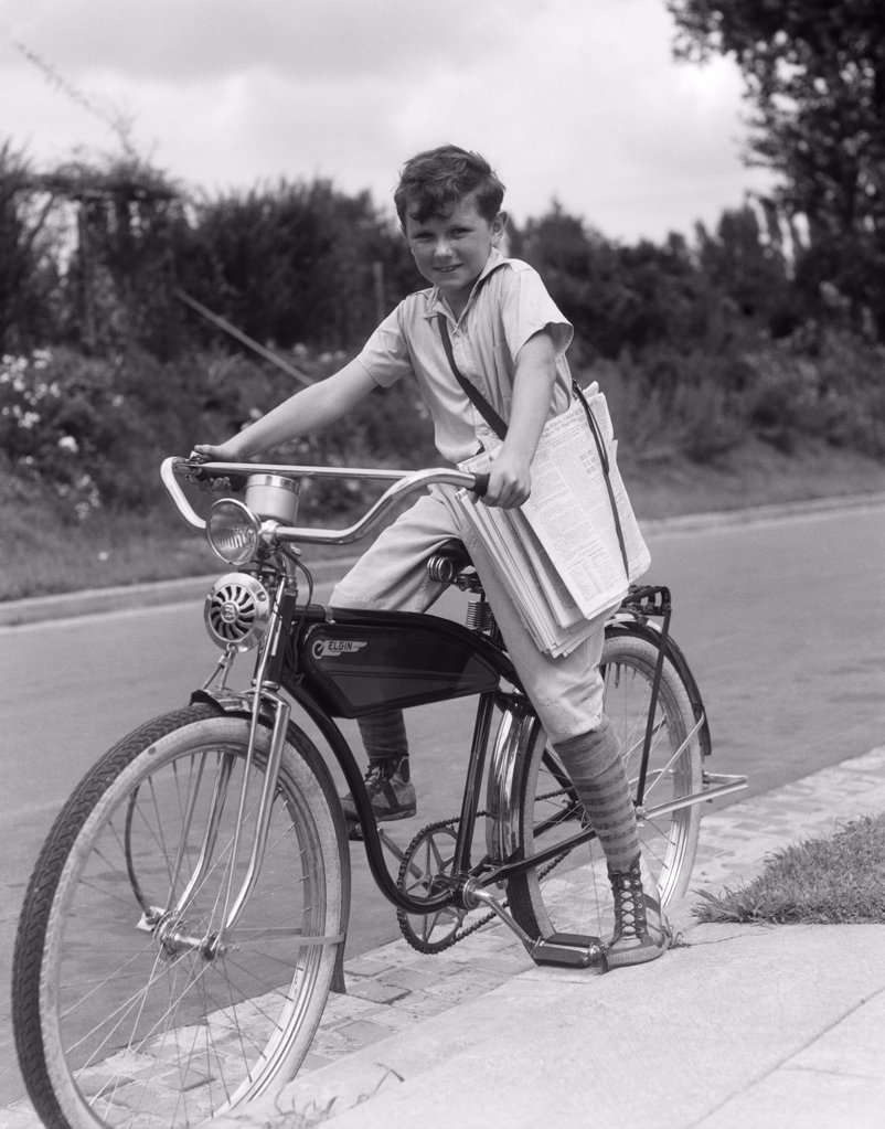 Stock Photo: 4186-4235 1940S Boy On An Elgin Bike Carrying Newspapers In A Sling Wearing Knee Socks And Sneakers