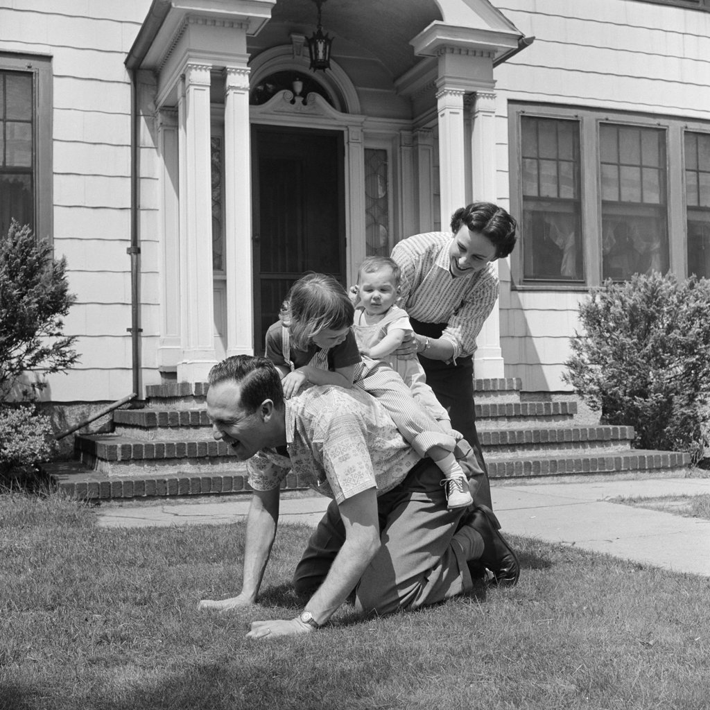 1950S Family Front Lawn House Two Kids Riding Father Piggyback Mother Helping Toddler Baby : Stock Photo