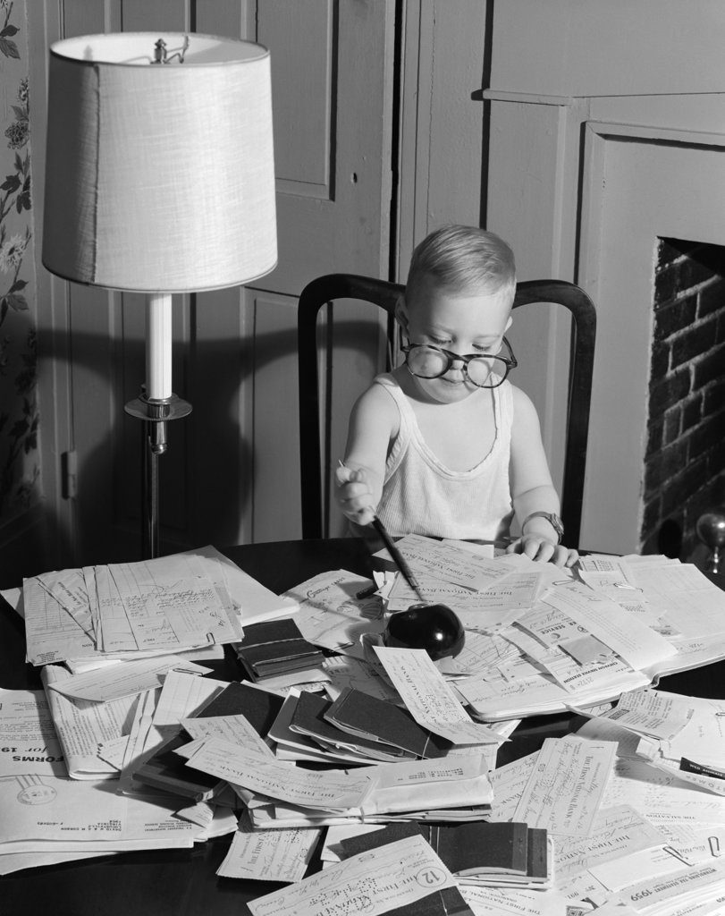 Stock Photo: 4186-4310 1960S Young Boy At Desk Wearing Glasses And Undershirt Examining Personal Financial Documents Receipts Tax Forms Irs Audit