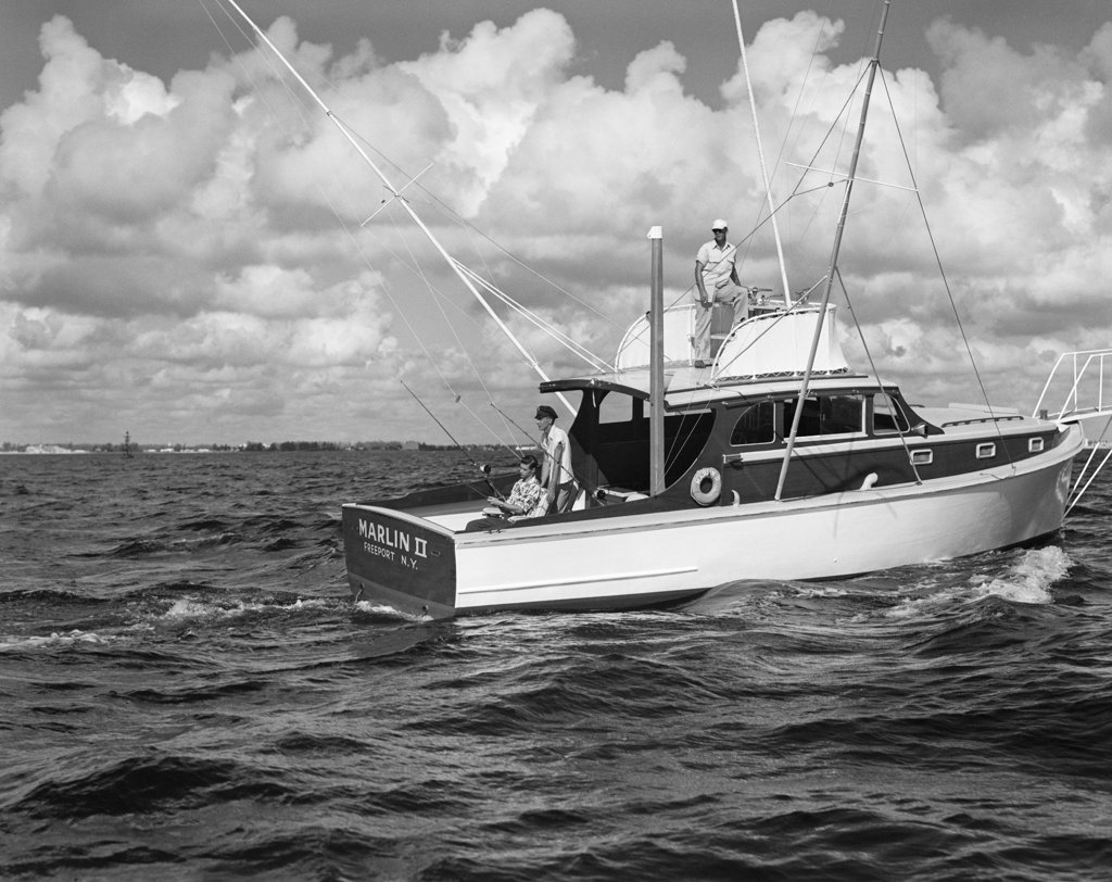 Stock Photo: 4186-476 1950S Group Of 3 Men Trolling Off Of Fishing Boat In Gulf Stream