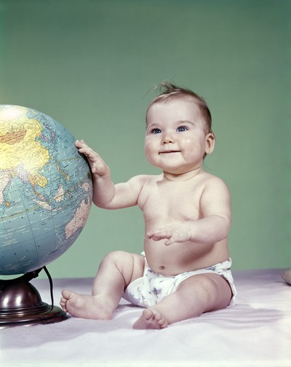 Stock Photo: 4186-4809 1960S Smiling Baby Girl Sitting In Diapers Hand Touching World Globe