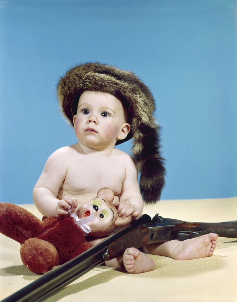 Stock Photo: 4186-4919 1960S Baby Boy Wearing Coonskin Cap With Stuffed Animal And Shotgun Gun