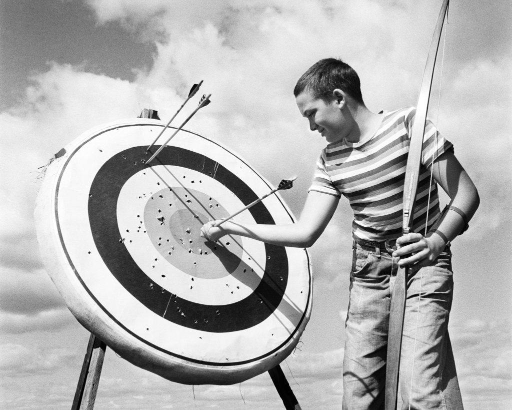 1960S Boy Jeans Striped T-Shirt Holding Bow & Pulling Arrow Out Of Target Bull'S-Eye   : Stock Photo