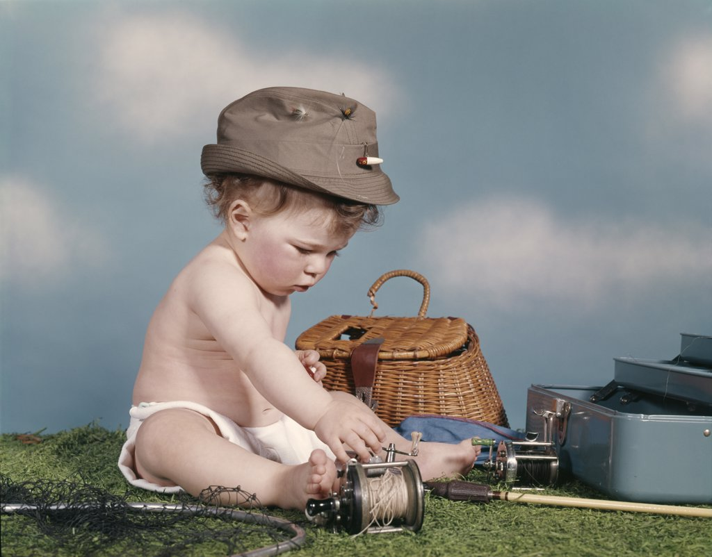Stock Photo: 4186-5074 1960S Baby Ready To Go Fishing Wearing Hat Surrounded By Tackle Box Fishing Rod Net Basket