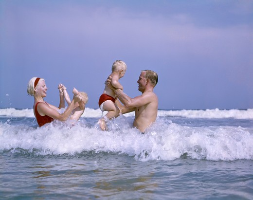 1970S Family Playing In Ocean Surf : Stock Photo