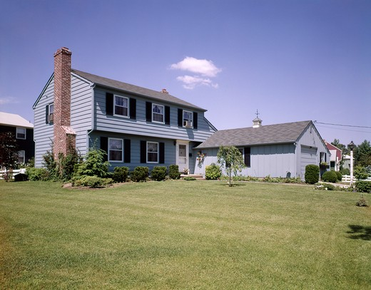 Stock Photo: 4186-5191 1960S Two Story Suburban Colonial House Gray Siding Shutters Large Lawn