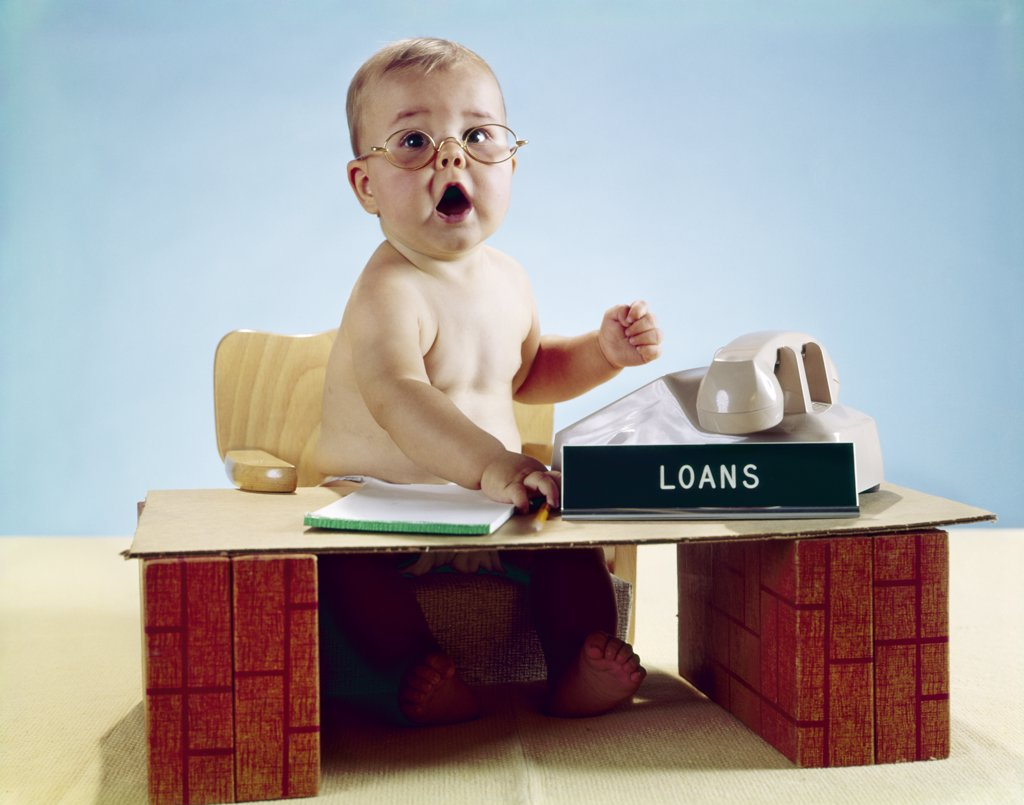 Stock Photo: 4186-5257 1960S Baby Businessman Sitting At Toy Desk Loans Sign Wearing Eyeglasses