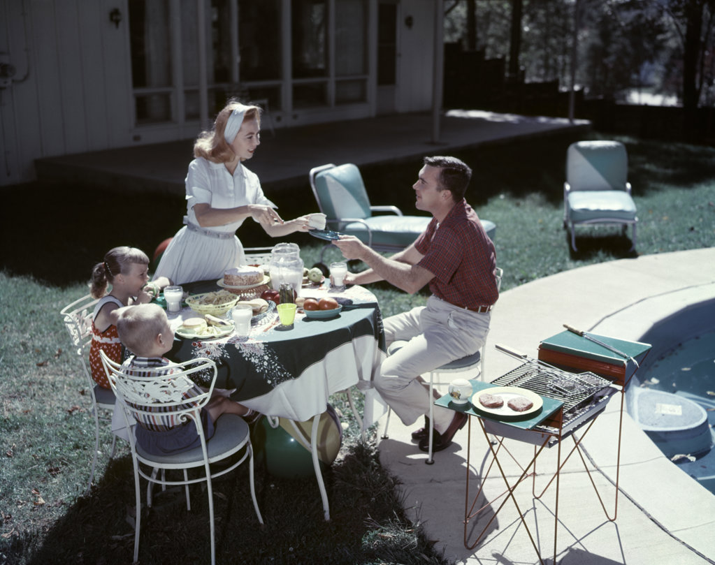 Stock Photo: 4186-5385 1950S Family In Backyard Having Picnic From Grill Near Swimming Pool