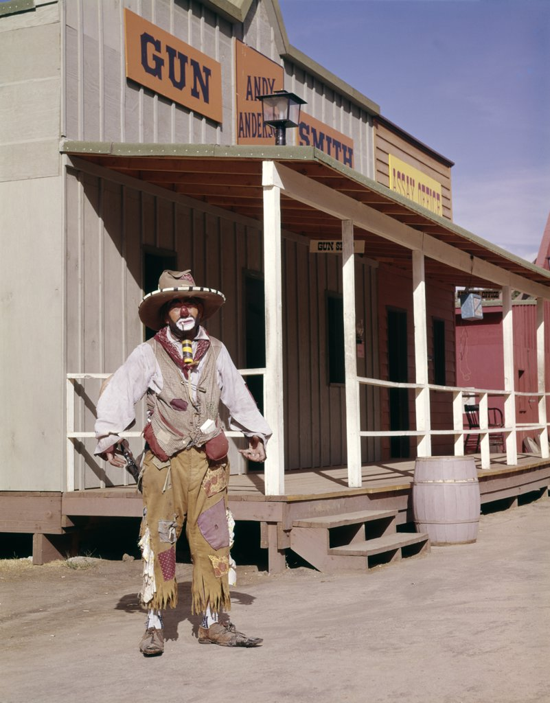 Stock Photo: 4186-5461 1960S Sad Clown In Cowboy Costume Standing In Street Of Western Frontier Town