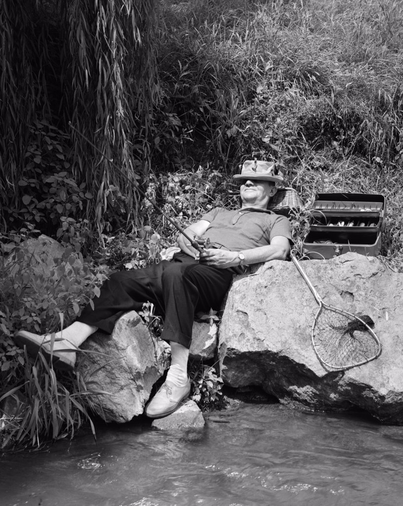1950S Lazy Fisherman Lying Back On Rock With Hat Pulled Over Eyes Fishing In Creek : Stock Photo