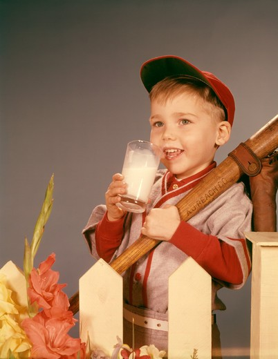 Stock Photo: 4186-6185 1950S 1960S Boy Drinking Milk Wearing Baseball Uniform  By Picket Fence
