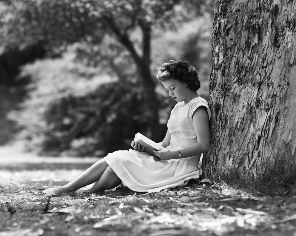 Stock Photo: 4186-630 1950S Young Woman Reading Book Sitting Under Tree