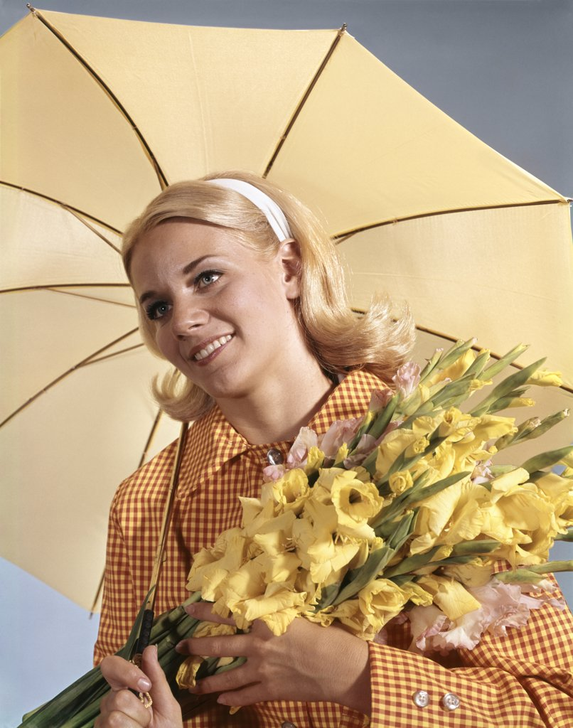 Stock Photo: 4186-6536 1960S Smiling Blond Woman Umbrella Holding Bouquet Yellow Gladiolas Spring