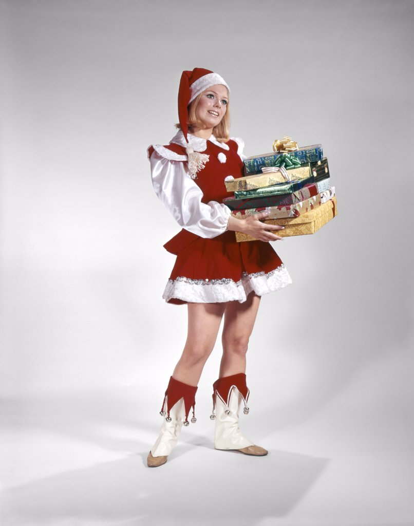 Stock Photo: 4186-6726 1960S Young Woman In Christmas Santa Helper Red And White Costume And Cap Holding Pile Of Gift Wrapped Presents
