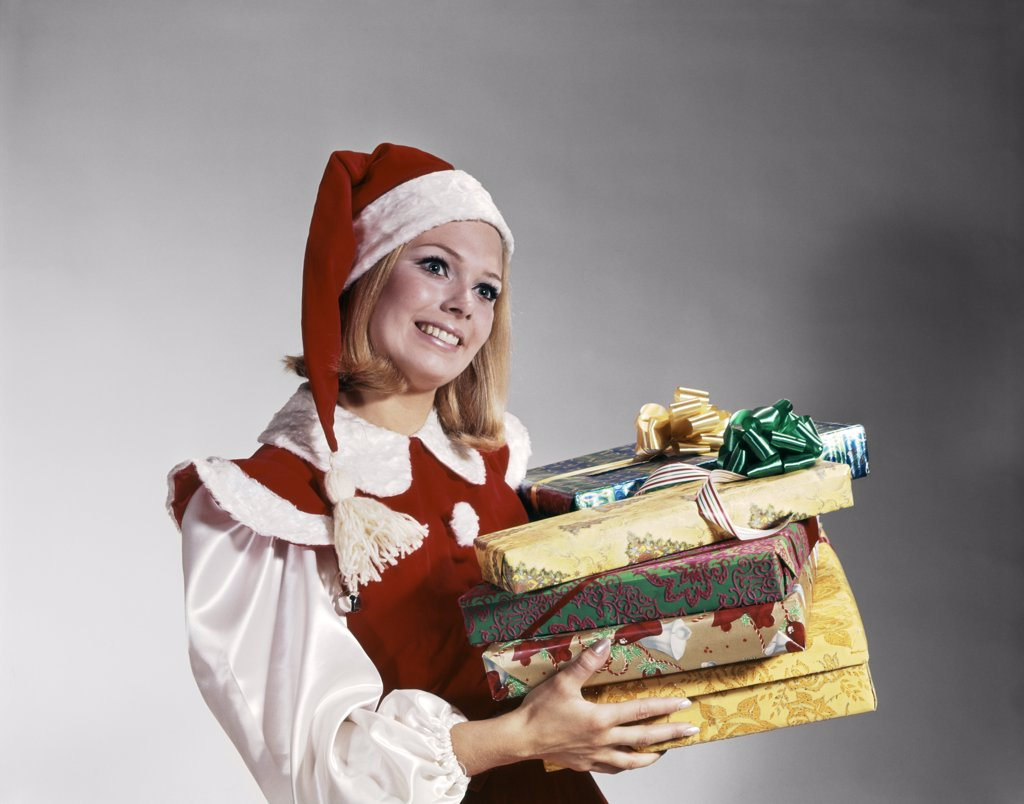Stock Photo: 4186-6728 1960S Young Woman In Red And White Santa Helper Costume And Hat Holding Pile Of Wrapped Christmas Presents Studio