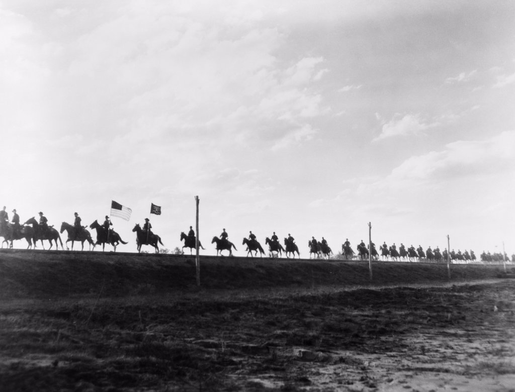 Stock Photo: 4186-682 Movie Still Single File Line Of United States Army Cavalry On Horseback In Silhouette On The Horizon
