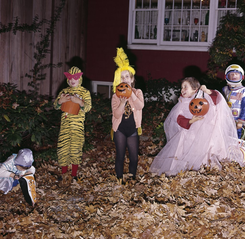 1970S Group Of Five Boys And Girls In Halloween Costumes Holding Trick Or Treat Pumpkins And Bags In Front Yard Of House : Stock Photo