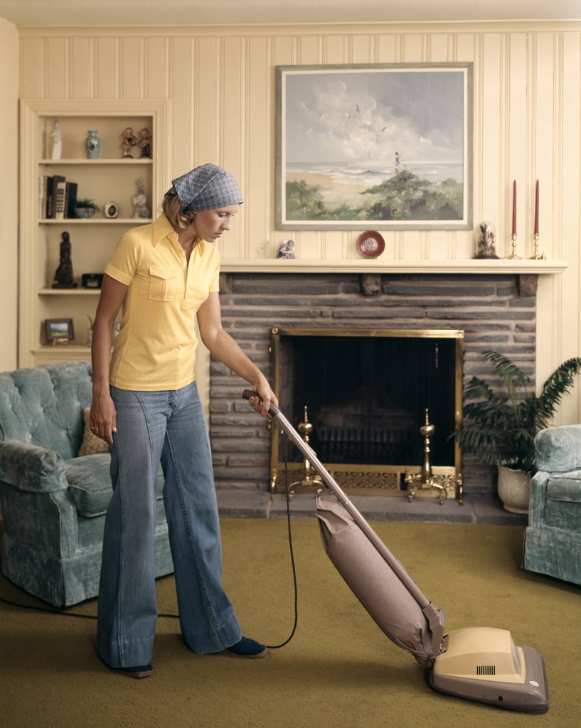 Stock Photo: 4186-7189 1960S Woman Wearing Head Scarf And Bell Bottom Pants Cleaning Living Room With Upright Vacuum Cleaner