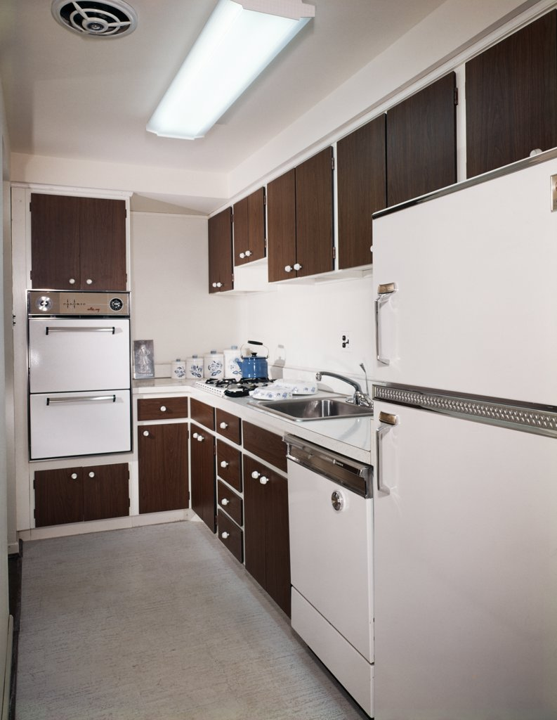 1970S Narrow Galley Style Kitchen With Dark Wooden Cabinets And White Appliances : Stock Photo