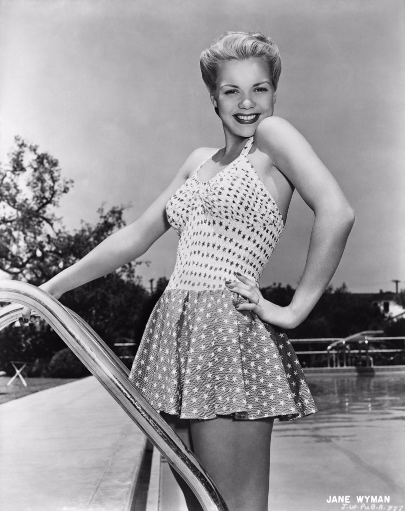 Stock Photo: 4186-790 1940S Actress Jane Wyman Posing In Bathing Suit On Swimming Pool Ladder
